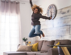 happy person jumping on their couch