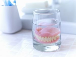 Dentures sitting in a glass of solution on a bathroom counter